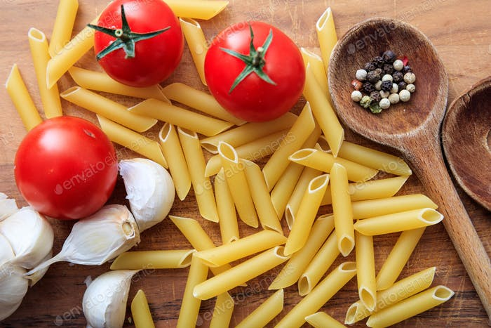 Raw penne pasta with tomatoes and garlic