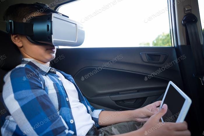 Teenage boy using virtual reality headset with digital tablet