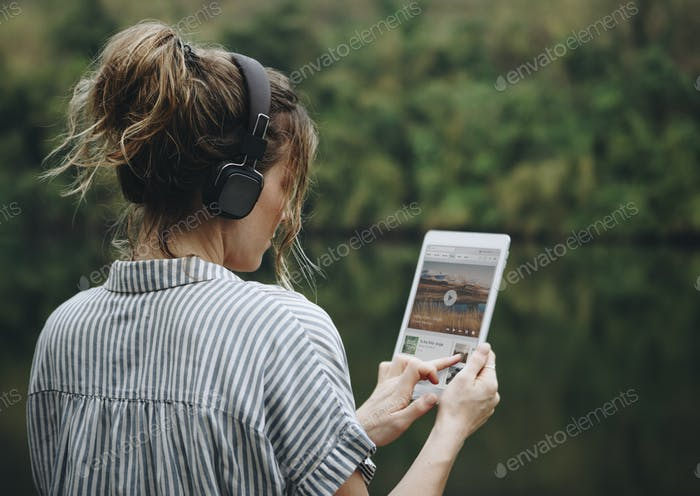 Woman alone in nature listening to music with headphones