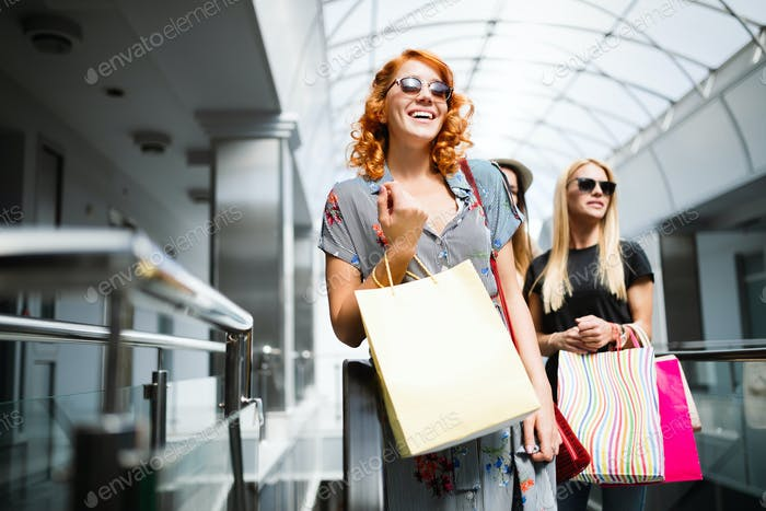Beautiful young woman with bags in shopping center