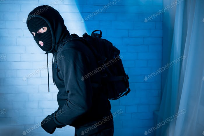 Sneaky burglar ready to steal something at home