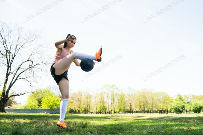 Young female soccer player practicing on field.