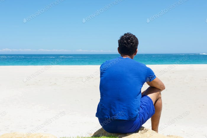 One man sitting alone at the beach