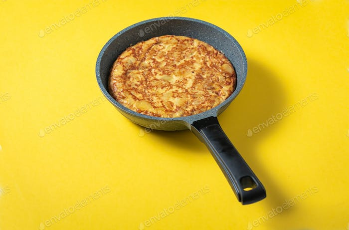 tortilla de patatas on skillet on yellow background, typical spanish dish.