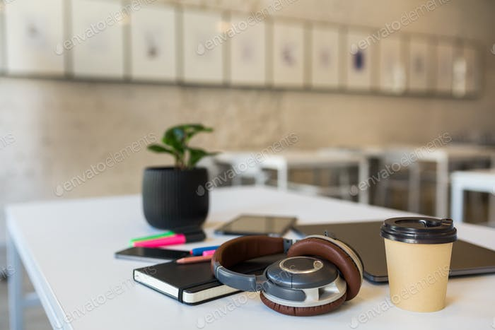 modern different office stationery on white table in co-working office, freelancer workplace