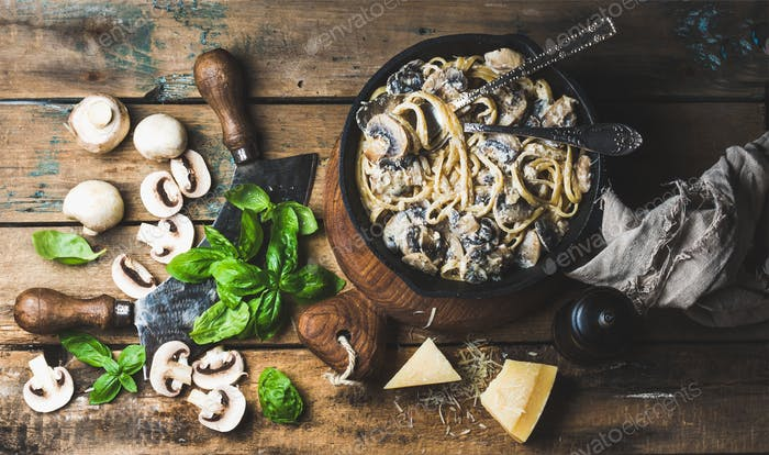 Mushroom pasta spaghetti in iron pan served with parmesan, basil