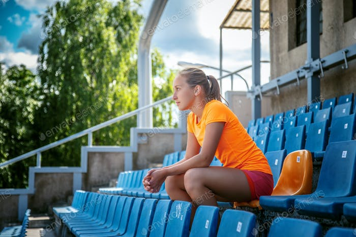 Slim female in orange sportswear.