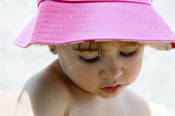 Close-up potrait of adorable little girl wearing sun hat