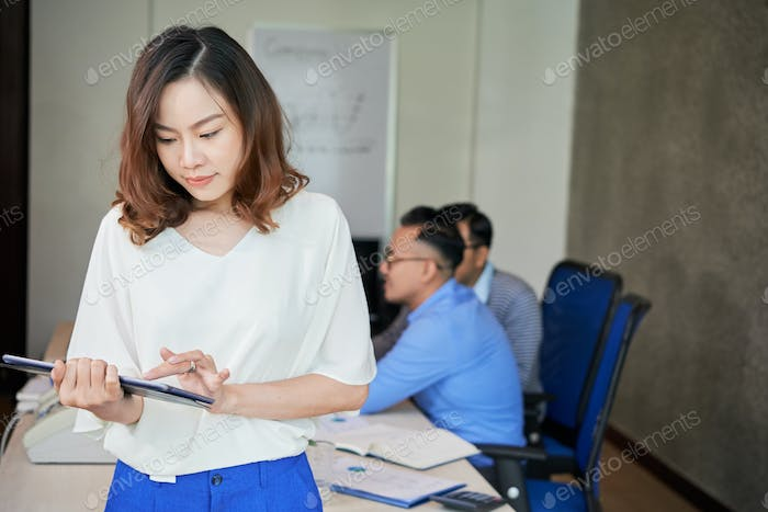Young ethnic woman using tablet in office with colleagues