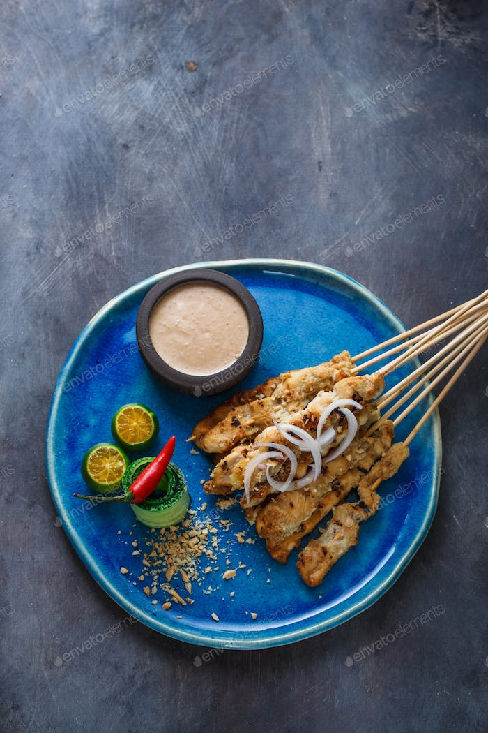 Indonesian chicken skewers sate with peanut sauce and salad, top view, copyspace