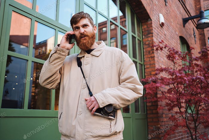 Young bearded man angrily talking on cellphone outdoor