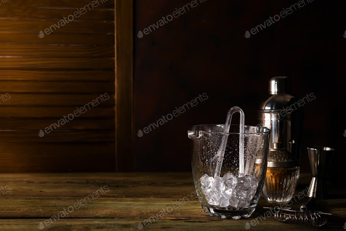 Glass ice bucket and Different cocktails in glass with Bar accessories on dark wooden background