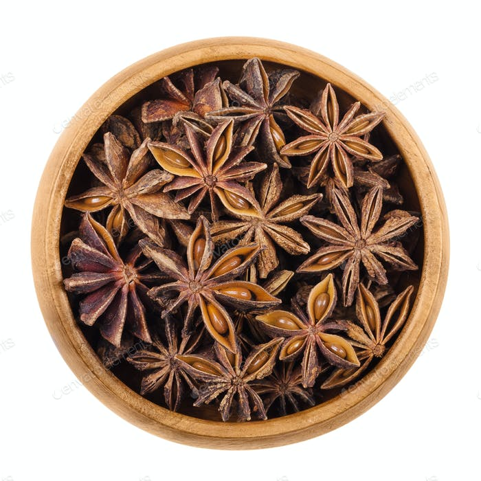 Star anise seeds in a wooden bowl over white