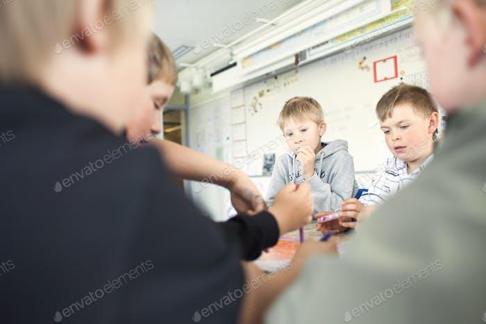 Elementare Jungen, die zusammen im Klassenzimmer studieren
