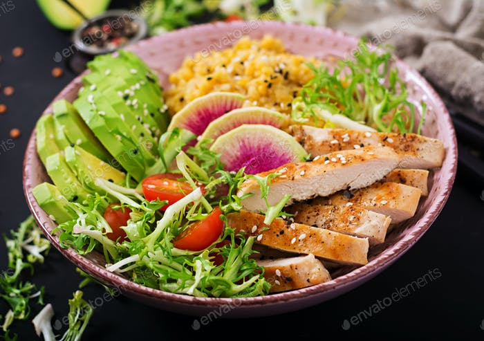 Healthy salad with chicken, tomatoes,  avocado, lettuce, watermelon radish and lentil