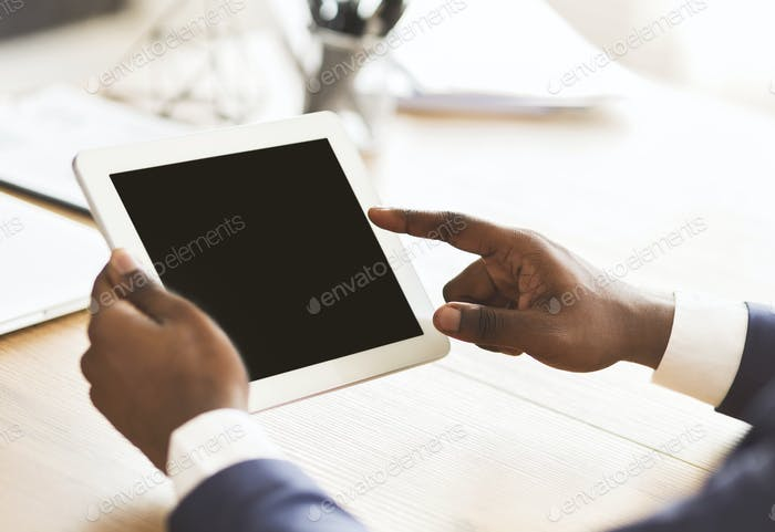 Schwarzer Mann mit digitalem Tablet mit leerem Bildschirm
