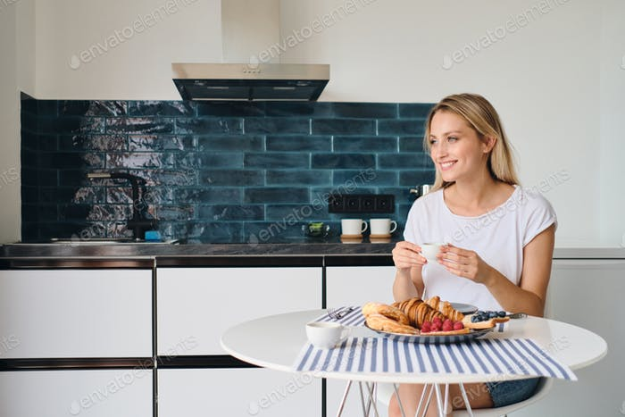 Young smiling woman happily looking aside with cup of coffee sitting at the table having breakfast