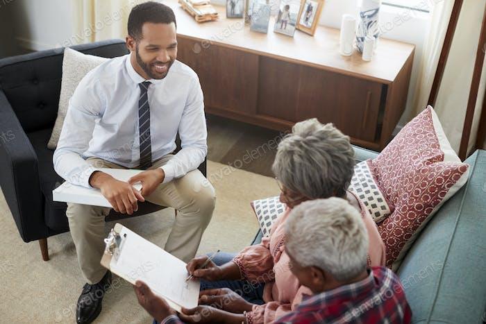 Seniorenpaar Treffen mit männlichen Finanzberater zu Hause und Unterzeichnung Dokument