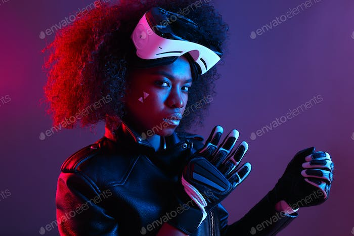 Stylish curly dark haired girl dressed in black leather jacket and gloves poses with the virtual