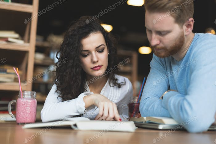 Young students spending time in coffee shop reading books