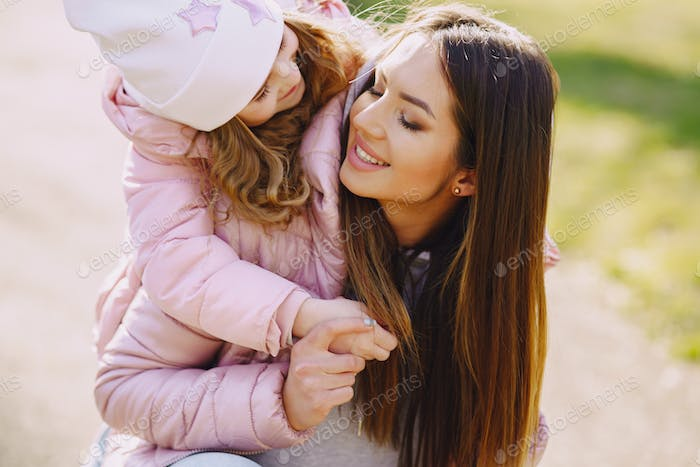Mother with daughter playing in a spring park