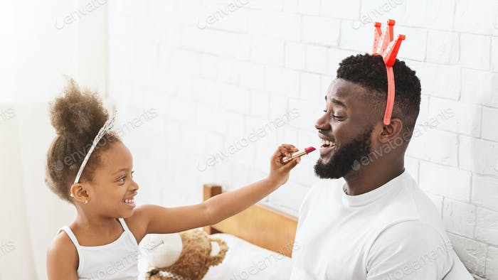 African father and preschool daughter having fun together