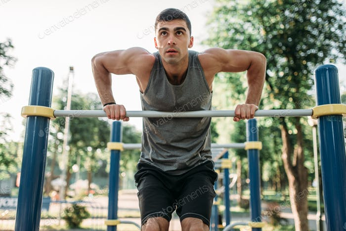 Man doing exercise on horizontal bar outdoor