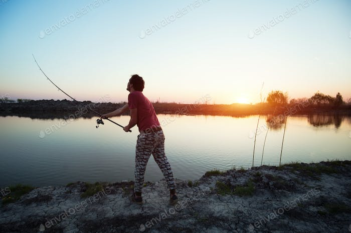 Young man fishing on a lake at sunset and enjoying hobby