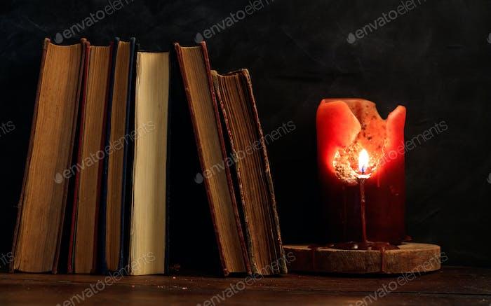 Vintage Bücher und Kerze auf dunklem Hintergrund