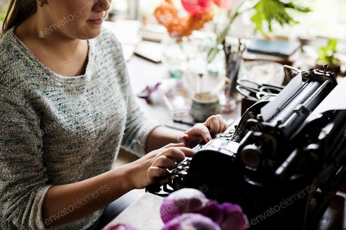 Woman typing typewriter on the table