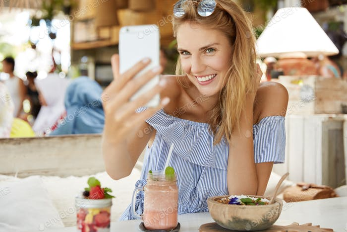 Attractive female model with stylish sunglasses on head, makes selfie photo on mobile phone, publish