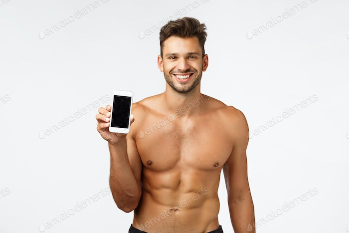 Technology, advertise and fitness concept. Sexy smiling strong, masculine shirtless athlete, holding