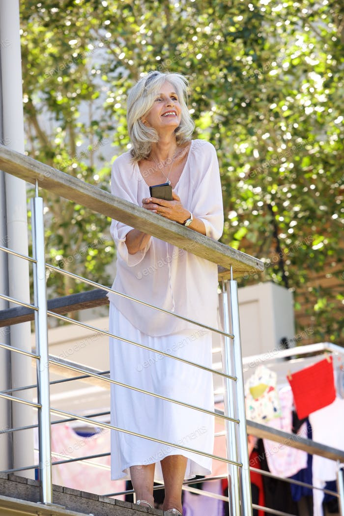 smiling older woman standing on balcony with smart phone