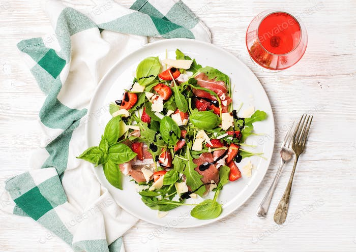Summer arugula, prosciutto, strawberry salad with glass of rose wine