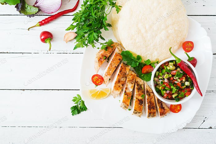 Grilled chicken breast with fresh tomato salsa and pita. Top view