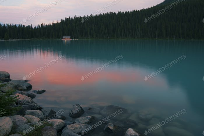 Forest treetops reflecting in still remote lake
