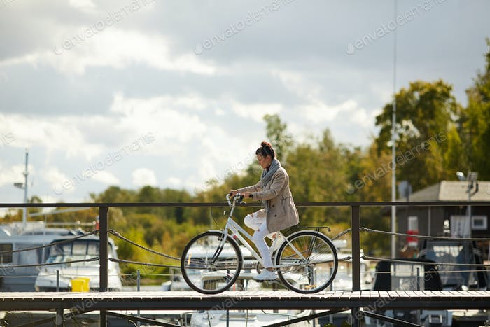 Concentrated woman in coat riding bike carefully on pier