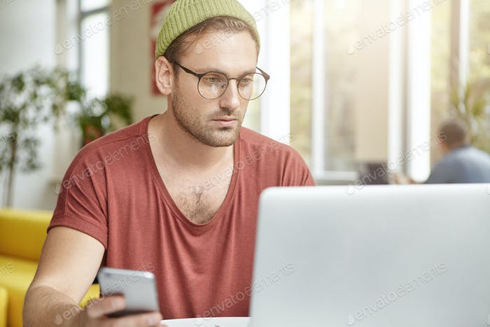 Modern technologies, networking, ecommerce and occupation concept. Serious bearded freelancer in sty