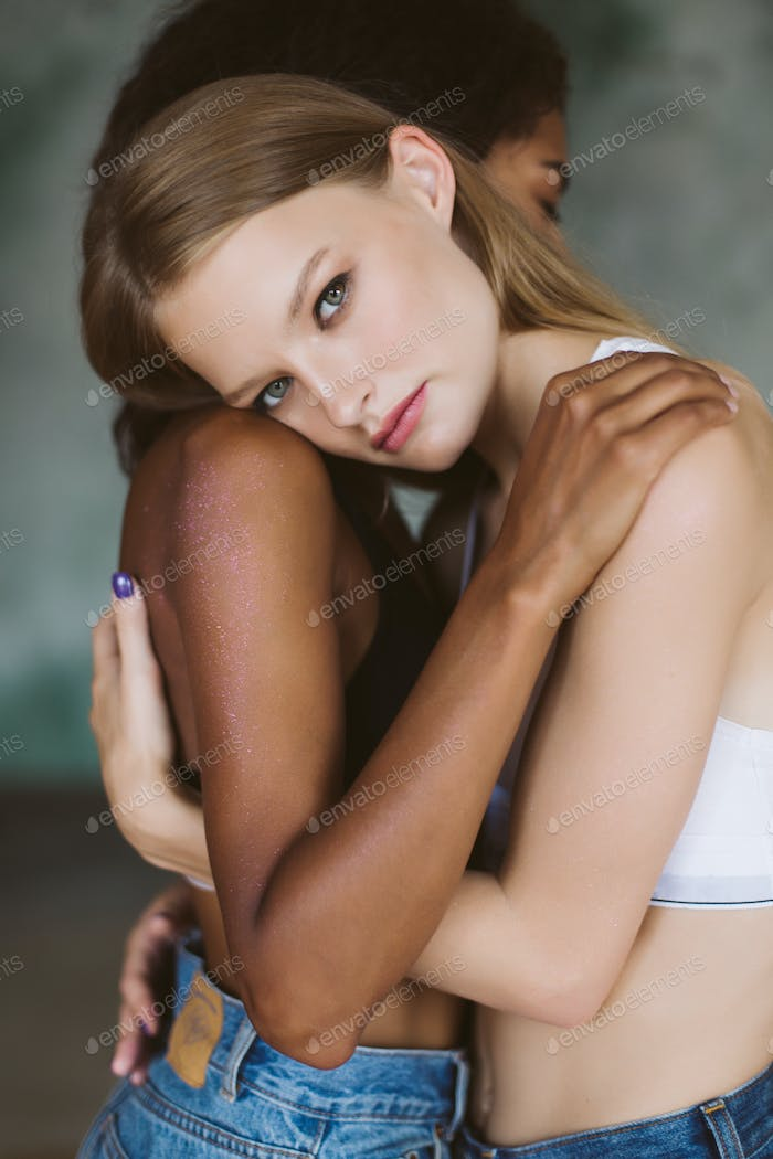 Young pensive woman with blond hair in top hugging african ameri