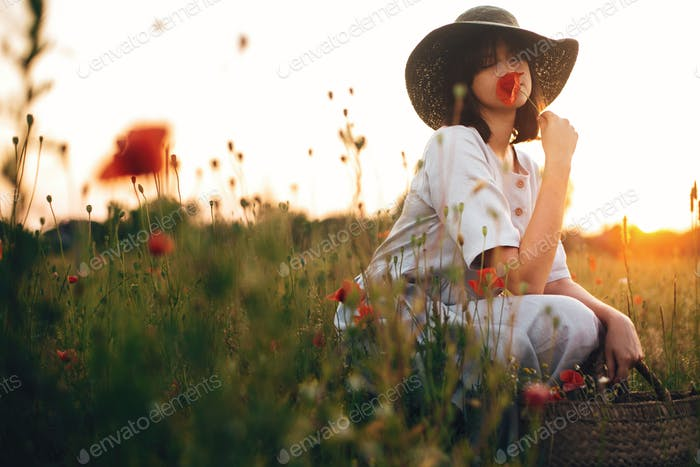Stylish girl in linen dress smelling poppy flower in meadow in sunset light