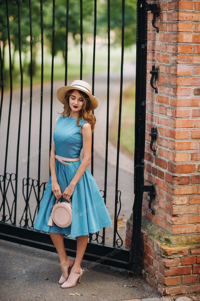 Модная девушка в синем платье и элегантной шляпе на улице