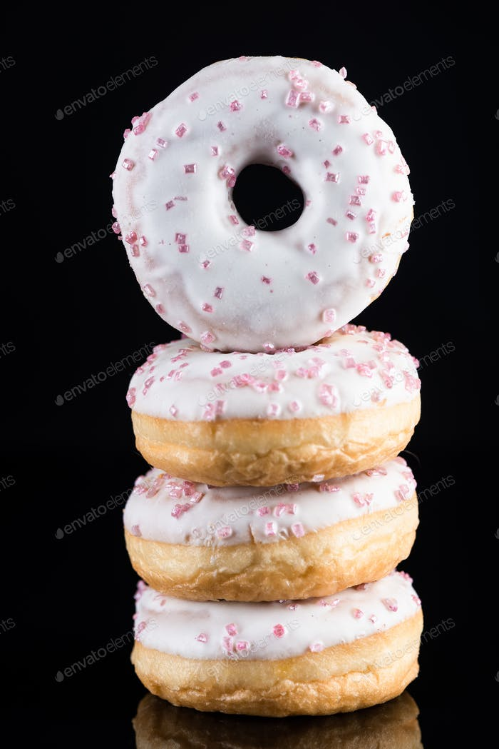 White Chocolate  Donuts or Doughnuts Tower on Dark Background. Copy Space for Text