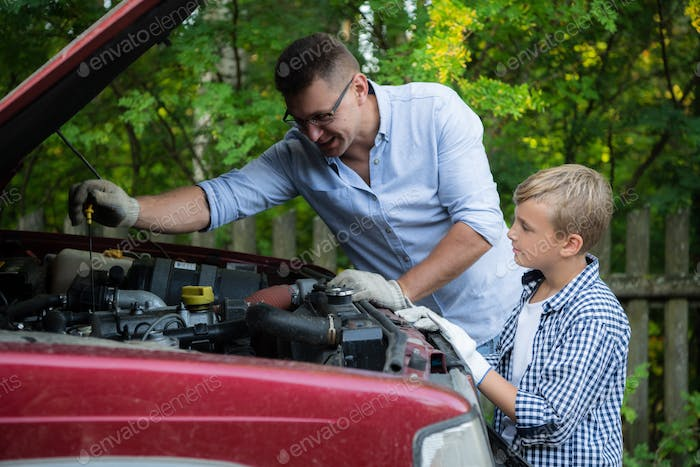 Father and son are repairing the car outdoors. Auto repair concept