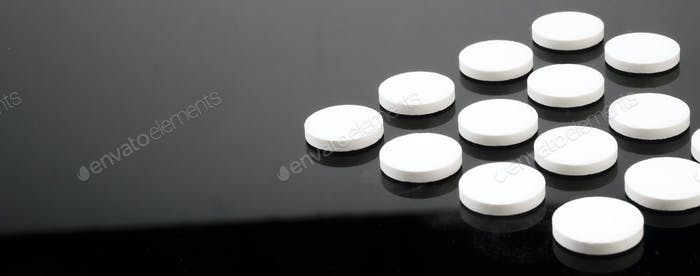 Some white pills aligned isolated on black background, conceptual image