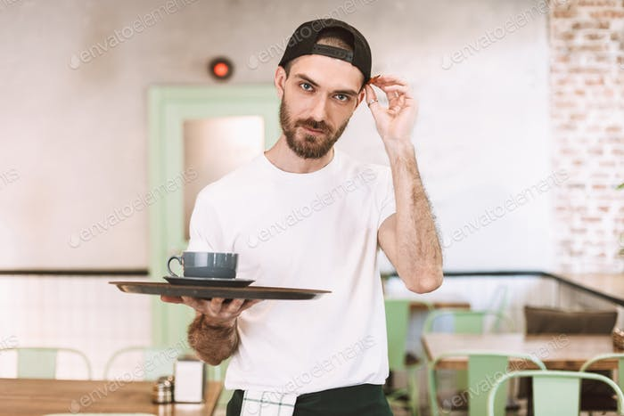 Young man in cap and white t-shirt holding tray with cup of coffee looking in camera in cafe