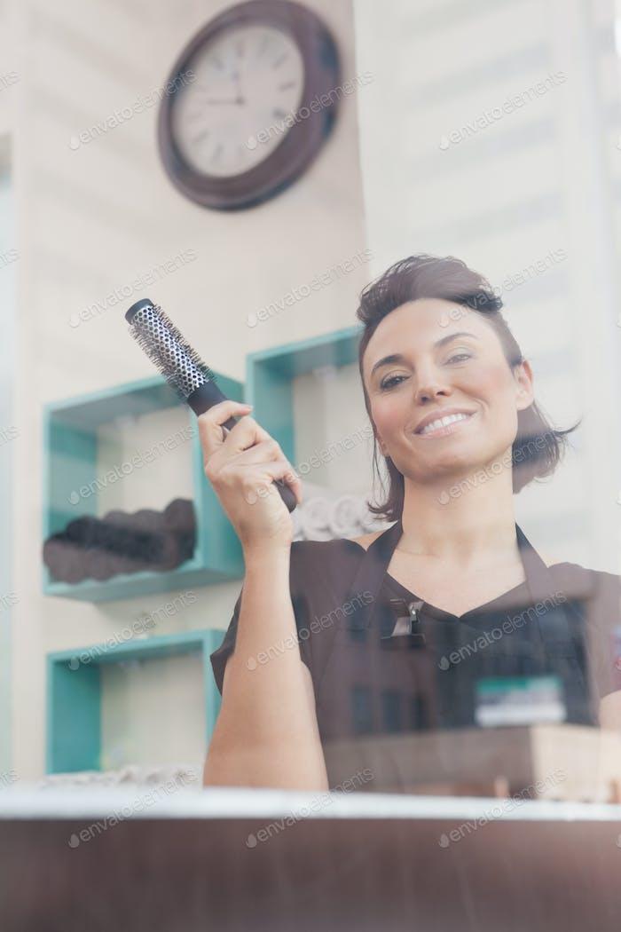 Smiling hairdresser holding hair brush in a salon
