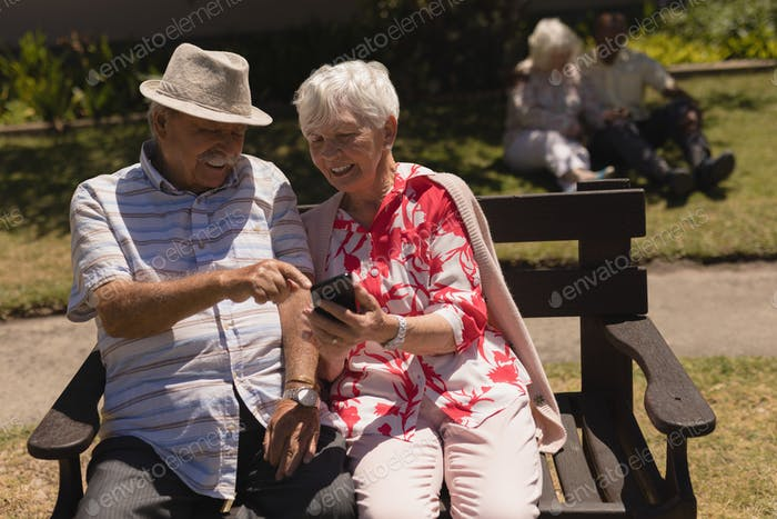 Front view of happy senior couple discussing over mobile phone and siiting on bench in garden