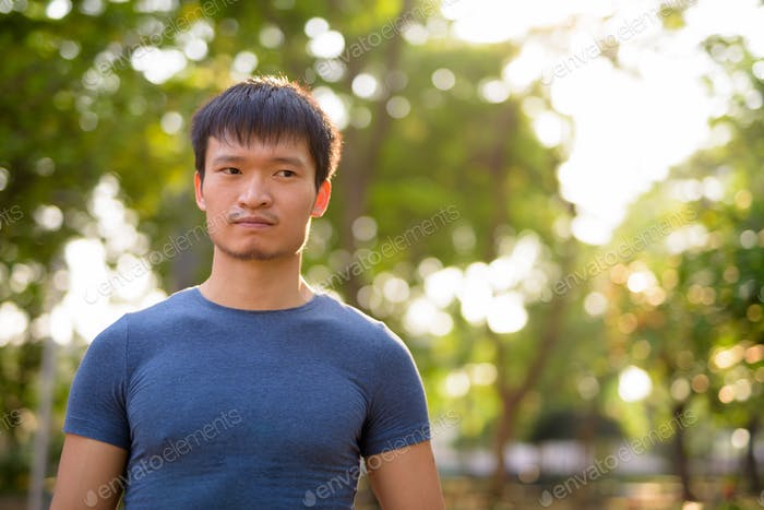 Portrait of young Asian man at the park outdoors