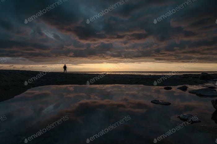 Mann Angeln bei Sonnenaufgang auf der Linie des Horizonts