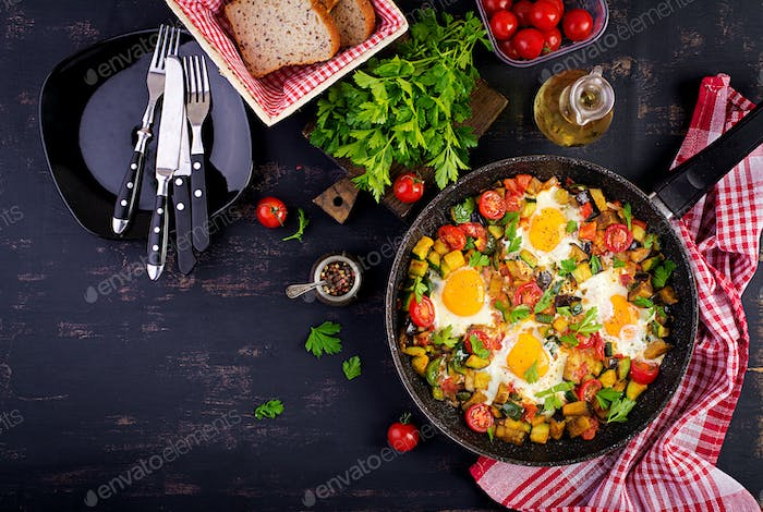Late breakfast - fried eggs with vegetables. Shakshuka. Arabic cuisine. Kosher food. Top view